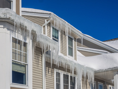 Ice dams with icicles hanging from an eavestrough of a house