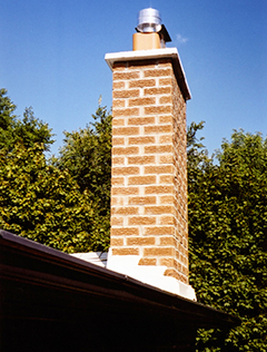 A red brick chimney structure in need of masonry repairs