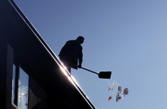 A man Shoveling snow from the Roof