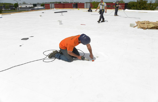 Roofing contractor inspecting for leaks on a flat roof