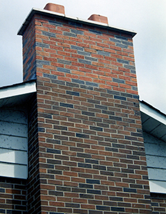 Red brick chimney structure outside a house
