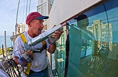 Roofer Caulking The Exterior Of a High-Rise Building