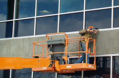 Roofer Caulking Exterior Of Commercial Building